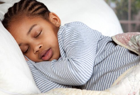 A young child sleeping in bed.