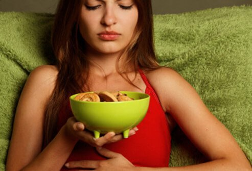 A woman experiences abdominal pain while eating.