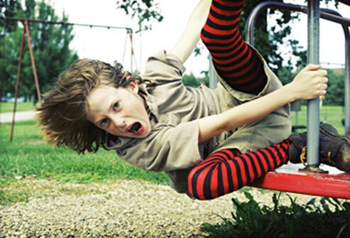 A girl yells while climbing on playground equipment.