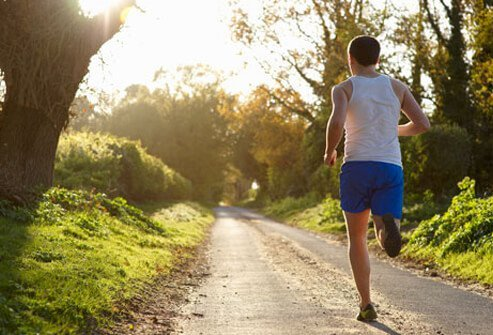 A man jogging in the woods, getting vitamin D.