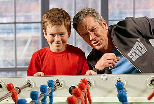 Photo of a man playing foosball with his grandson.