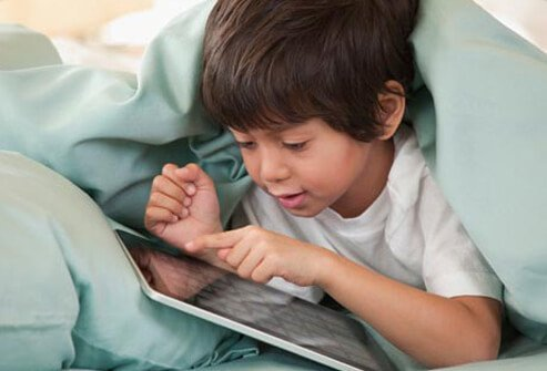 An autistic child playing with assistive technology.