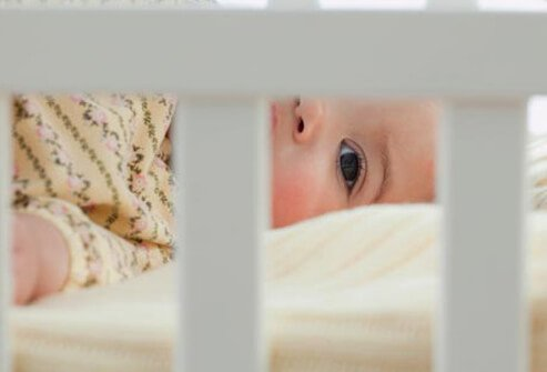 A baby with autism lying in a crib.