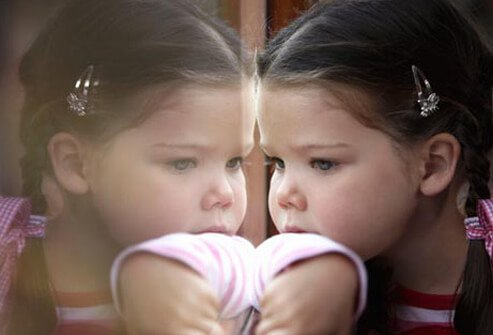 A toddler with autism looking out of a window.