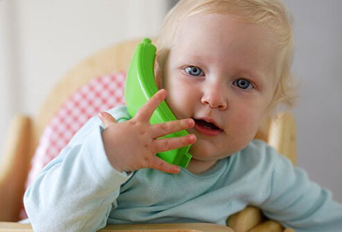 A baby talks on a toy phone.