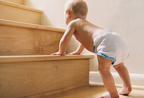 A baby tries to stand on the stairs.