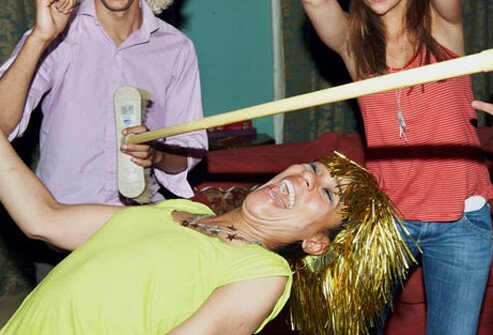 People at a party playing a game of limbo.