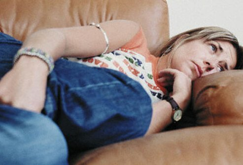 Photo of a woman with stomach pain on the couch.