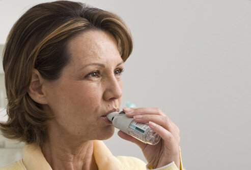 A woman using an inhalation spray to treat COPD.
