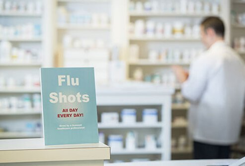 A pharmacy sign advertises flu shots to prevent the flu virus.