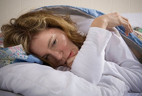 A fatigued woman suffering the symptoms of a cold or flu.