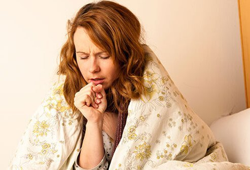 A young woman suffers from a cough, a symptom of a cold and the flu.