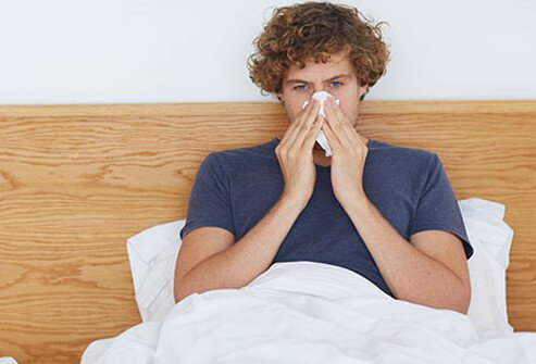 A man sick in bed with a stuffy nose has a cold.