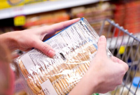 A woman reads the ingredients on a food package.