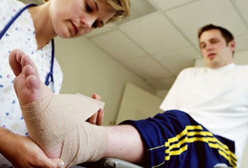 A nurse applies a compression bandage to a man's ankle to keep the swelling down.