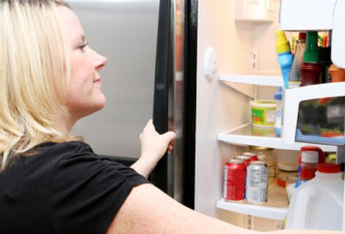Woman looking inside refrigerator.