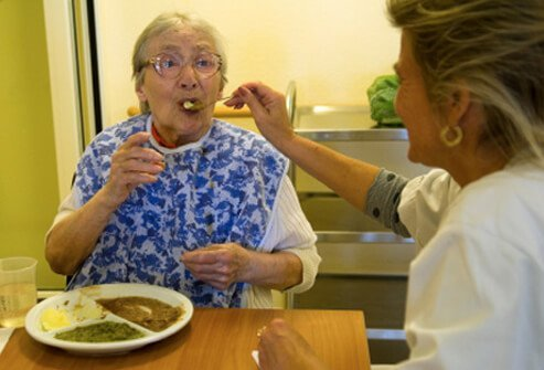 A caregiver feeding a senior woman with dementia.