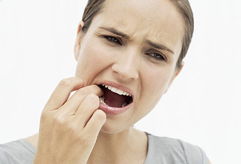 A woman with a toothache feeling her tooth with her finger.