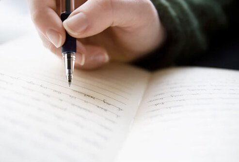Photo of a person writing in journal.