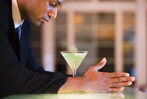 A depressed businessman stares at his martini.