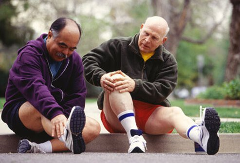 Two older men stretching before exercising.