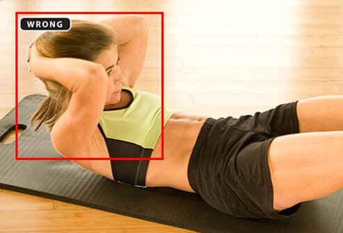 A trainer showing the improper form for crunches.