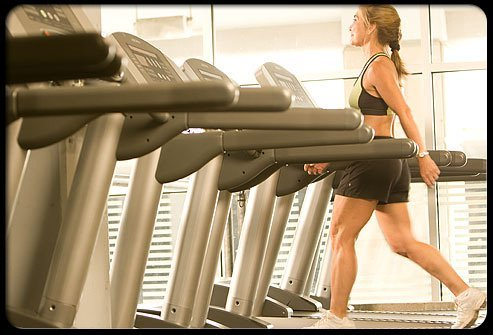 A woman walking on a treadmill at the gym.