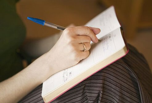 Photo of a woman writing in a journal, tracking her endometriosis symptoms.