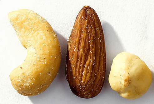 A close-up of a cashew, almond, and hazelnut.
