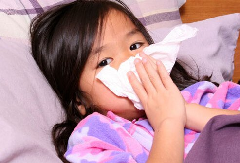 A young girl with a runny nose blows her nose in bed.