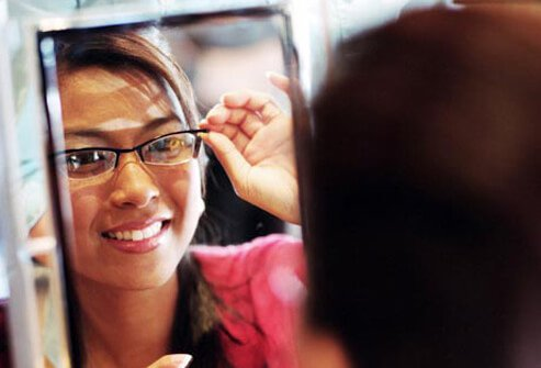 Photo of woman trying on glasses.