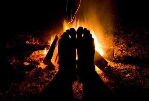 Feet warmed by campfire.