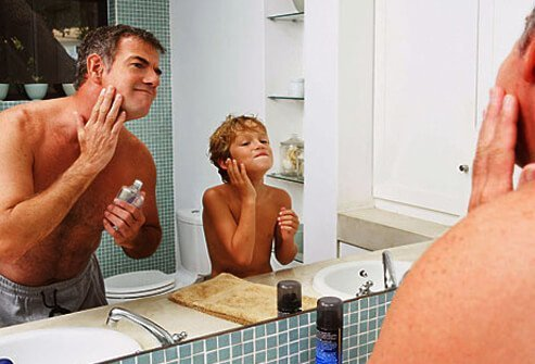 Photo of father and son applying aftershave.