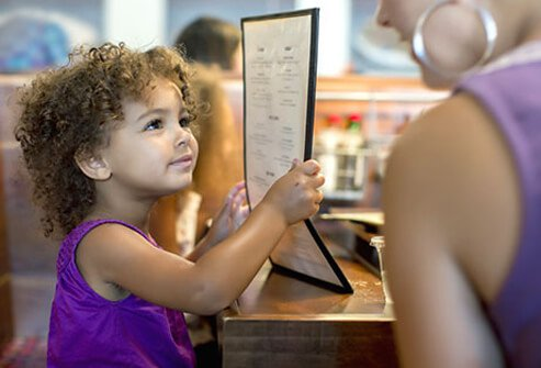 A toddler holds the menu at a restaurant.