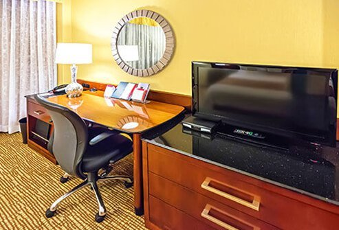 A hotel room desk and television.