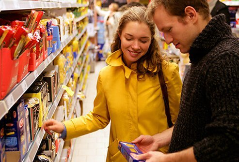 Couple in supermarket checking label of product.