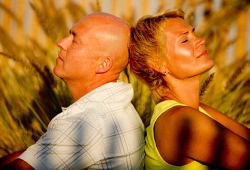 A bald man and woman with short hair enjoy the sun.