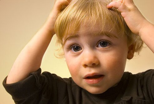 Photo of boy scratching head.