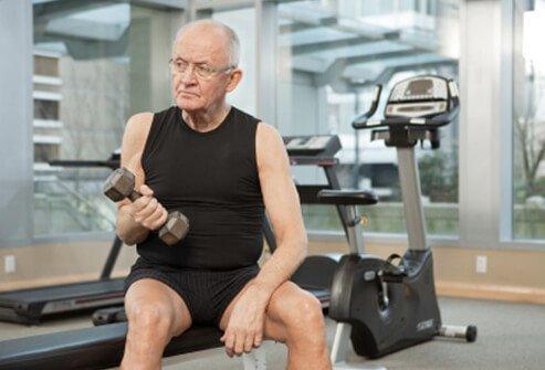 A senior man works out with weights in the gym.
