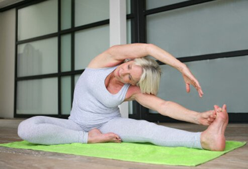 A senior woman does stretching exercises on the floor.