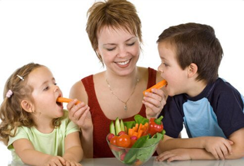 A mother feeds both of her children vegetables.