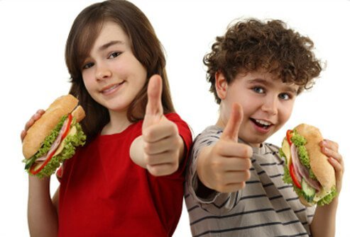 Siblings give a thumbs-up for their healthy sandwiches.