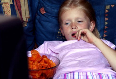 A girl snacks while watching TV.