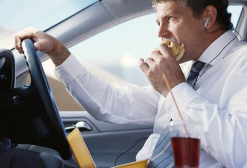 A businessman sitting in a car and eating fast food.