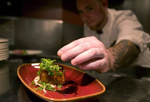 Photo of cook adding garnish to a food dish.