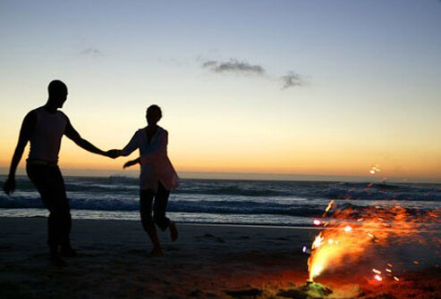 Photo of couple on beach by a fire.