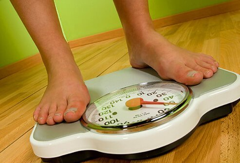 A person stands on a weight scale.