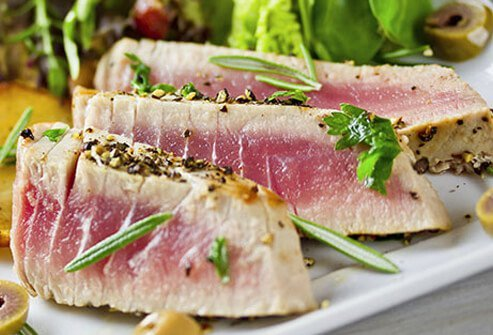 Fresh tuna steak paired with a small salad and potatoes.