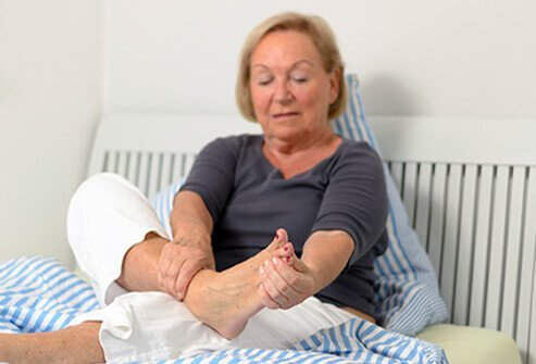 A woman examines her foot for an ingrown toenail.