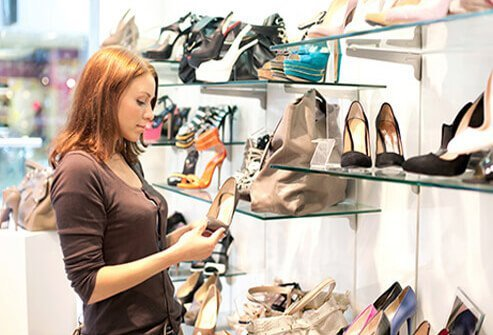 A woman shops for shoes that can support the foot and have a wide toe box.
